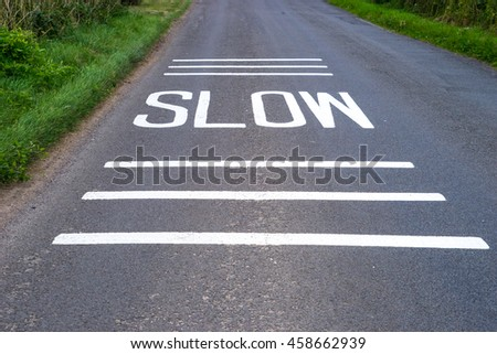 Slow Sign freshly painted on road  with lines above and below for emphasis - stock photo
