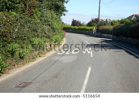 Slow sign on a bend in a Cornish road. - stock photo