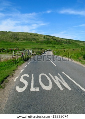 Slow sign on an English countryside road. - stock photo