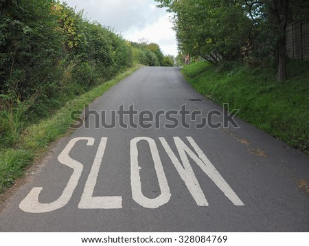 Slow sign painted on tarmac on a british road near a school - stock photo