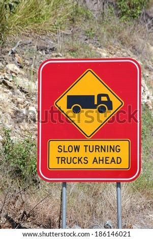 Slow Turning Trucks Ahead Sign 1 - stock photo