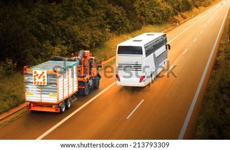 Slowly truck and speedy autobus on the highway. - stock photo
