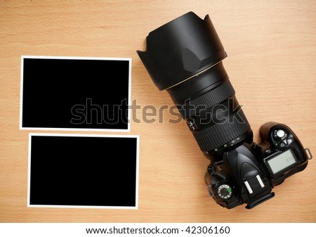 SLR Camera and blank photo prints on wooden desktop - stock photo