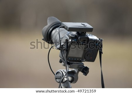 Slr camera on a tripod out in the fields - stock photo