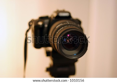 SLR camera with zoom lens on tripod