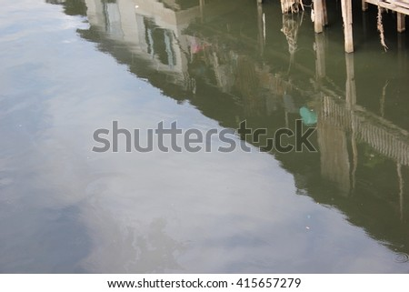 slum reflect on water - stock photo
