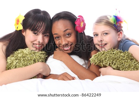 Slumber party for three teenage girl friends, a mixed race african american, oriental Japanese and blonde caucasian school mates all wearing flower or feather hair accessories. - stock photo