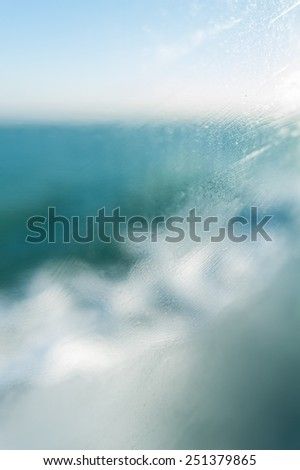 Slurred steamy glass and small water droplets on the endless blue ocean background - stock photo