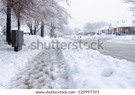 Slush and snow in the sidewalk in a cold winter day - stock photo