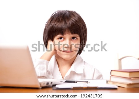 Sly boy at table with computer and books - stock photo