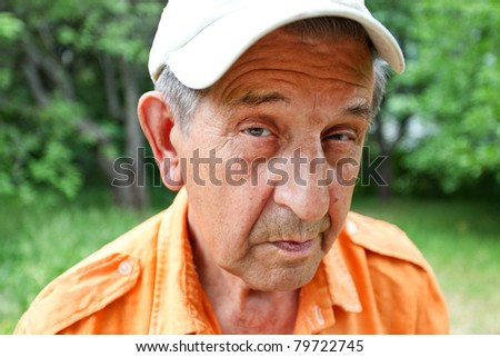 sly elderly man smiling - stock photo