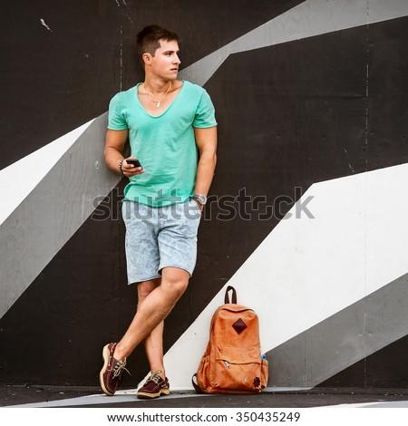 Slylish fashion man traveling with a bag - stock photo