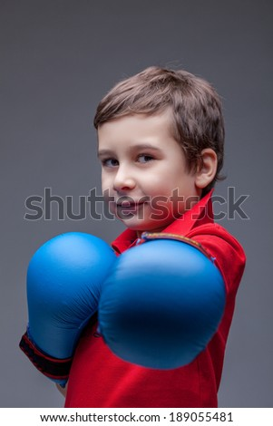 Slyly smiling young boxer posing looking at camera