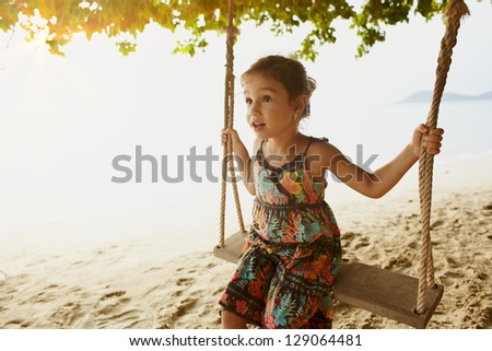 Smal girl swinging on sea coast