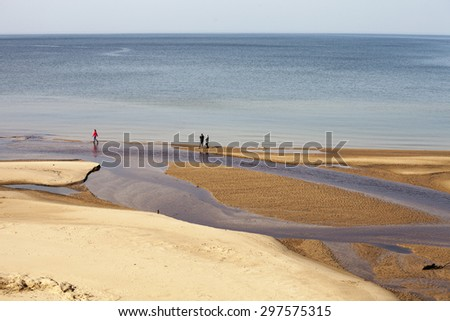 Smal river mouth flows in calm sea - stock photo