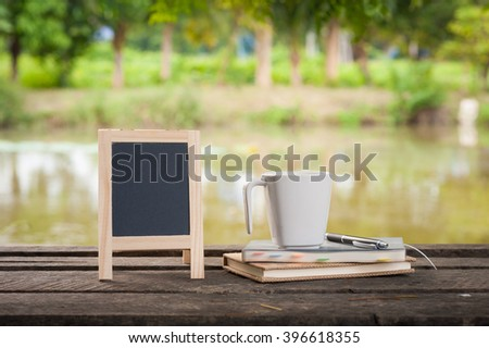 Small A-frame blackboard with blank area for text or message, notebooks and coffee cup on rustic wood table with rural lake view in blurry background at morning time