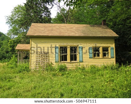 Small, abandoned house with overgrown grass.