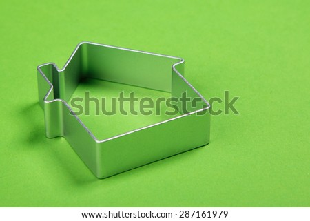 Small abstract model of house on green background