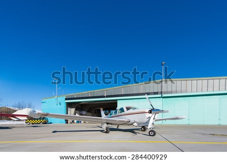 small aeroplane standing before aircraft hangar at blue sky - stock photo