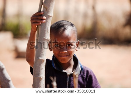 small African boy , outdoors, holding a branch - stock photo