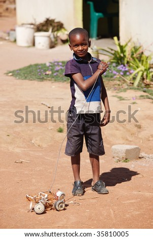 small African boy , outdoors, playing with a car made out of beer cans - stock photo