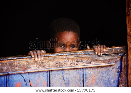Small African child behind the door of the village house, lomo look