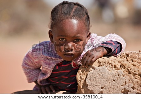 small African girl portrait , outdoors, playing on a broken wall - stock photo