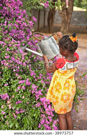 small african girl working in the garden watering the flowers - stock photo