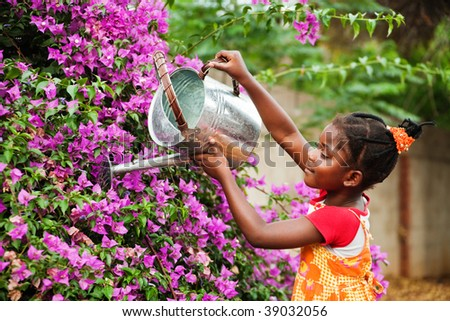 small african girl working in the garden watering the flowers, warm light - stock photo
