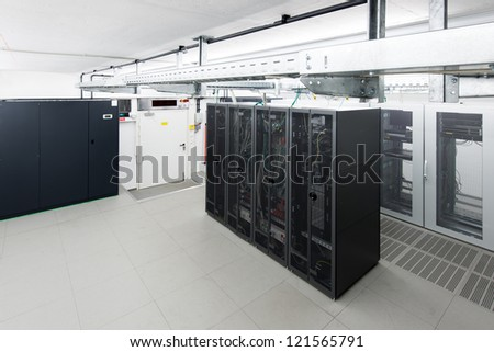 small air conditioned server room with black racks and climate control unit - stock photo