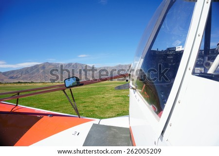 Small aircraft cockpit and wing close up, on rural airfield with the Benmore Range view ahead ready for take-off, Omarama, Otago New Zealand. - stock photo