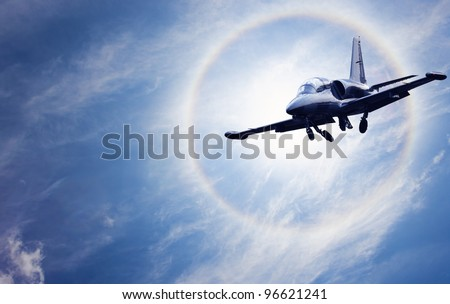 Small aircraft flying in front of the sun with halo - stock photo