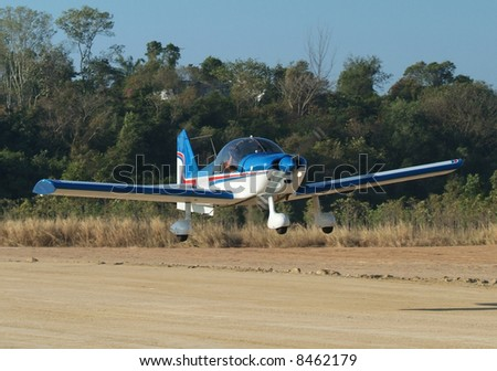Small aircraft landing on a dirt runway in a forest - stock photo