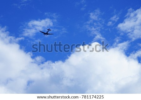 Small airplane in the blue sky with white clouds.