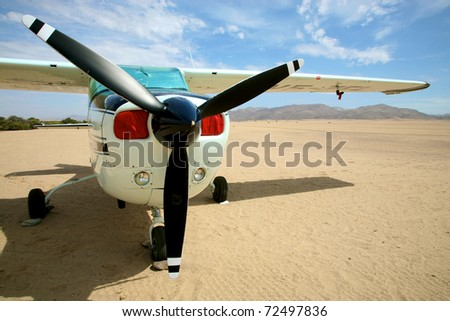 Small airplane in the desert of namibia with a blue sky and the sert all around - stock photo