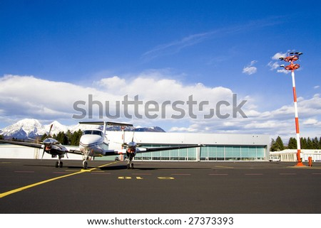 Small airplane on runway with hangar in background. - stock photo