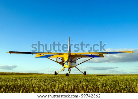 small airplane waiting on field - stock photo