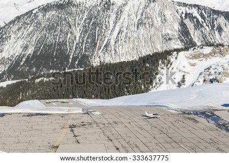 Small airport altiport on the side of a snowy alpine mountain in winter - stock photo