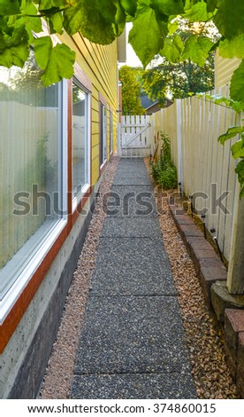 Small alley between yellow house and white fence with green grape leaves above. Convenient concrete pathway from back yard of the house to a street. Cozy walk path beside family house. - stock photo