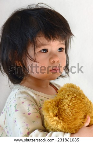 Small almost two years old child portrait. Teddy bear in hand. Mixed ethnicity, chinese with european. - stock photo