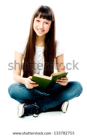 Small and beautiful girl reading a book - stock photo