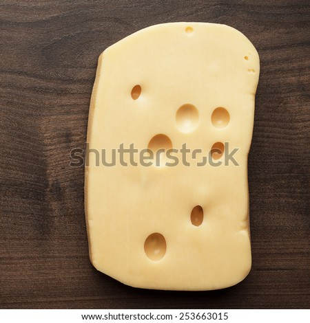 small and big pieces of cheese on wooden table - stock photo