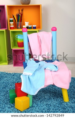 Small and colorful chair with baby clothes - stock photo