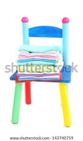 Small and colorful chair with baby clothes isolated on white - stock photo
