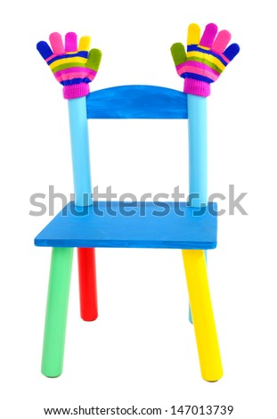 Small and colorful chair with baby mittens isolated on white - stock photo