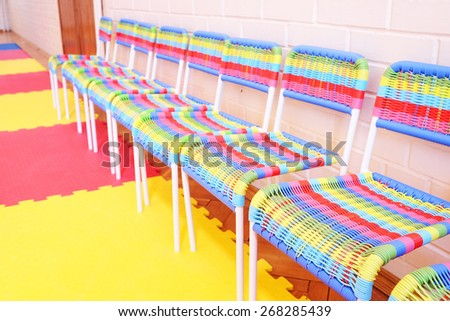 Small and colorful chairs in row - stock photo