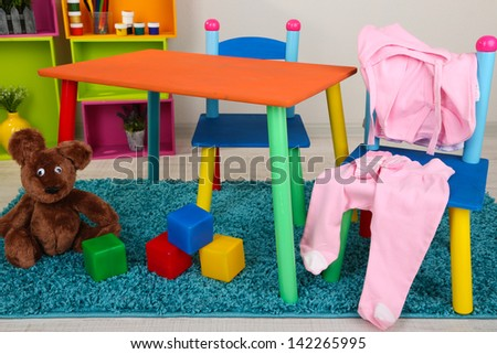 Small and colorful table and chairs with baby clothes - stock photo