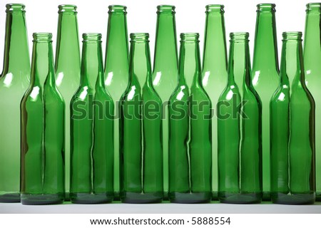Small and high green beer bottles. Concept of equality. Shallow DOF. - stock photo