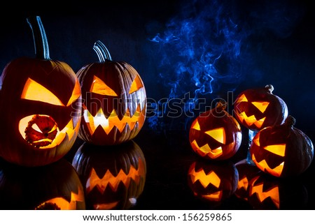 Small and large pumpkins for Halloween with candles on a black background - stock photo