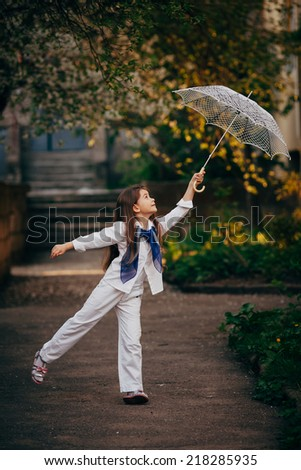 small and pretty girl dancing with lace umbrella in white suit
